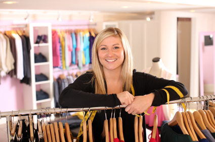 Lady leaning on rack of clothes in a dress shop