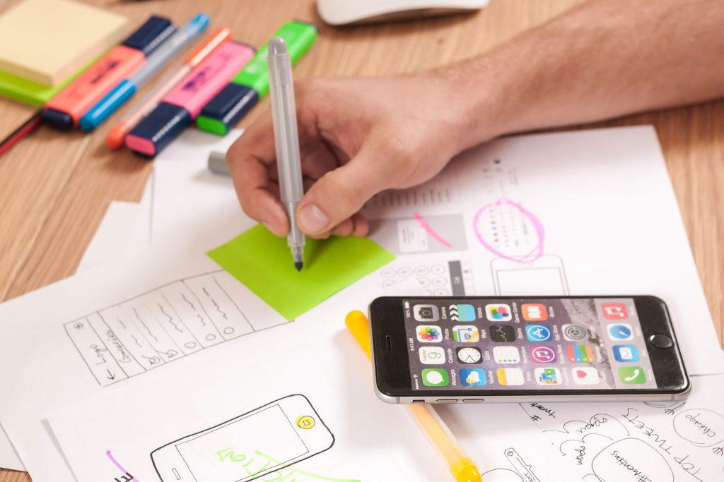 Man drawing sketches of mobile screens with mobile phone on table